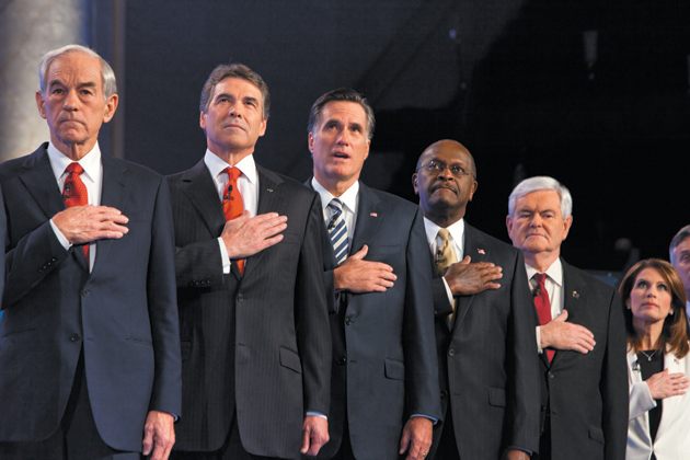 Republican presidential candidates Ron Paul, Rick Perry, Mitt Romney, Herman Cain, Newt Gingrich, and Michele Bachmann during the National Anthem before a debate, Washington, D.C., November 22, 2011