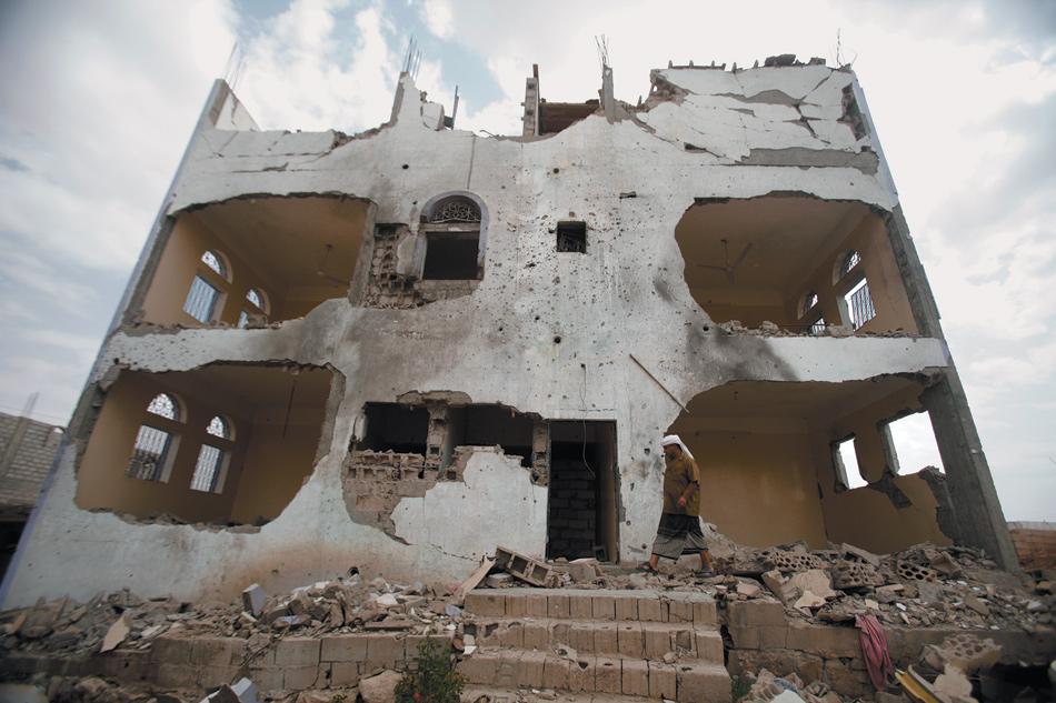 A tribesman near a building damaged by a US drone strike that targeted suspected al-Qaeda militants last year, Azan, Yemen, February 2013