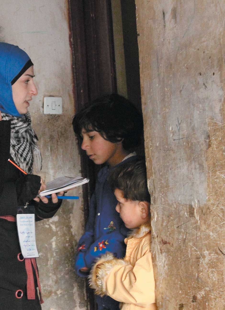 A health worker talking with a family in Aleppo before administering polio vaccinations, January 2014