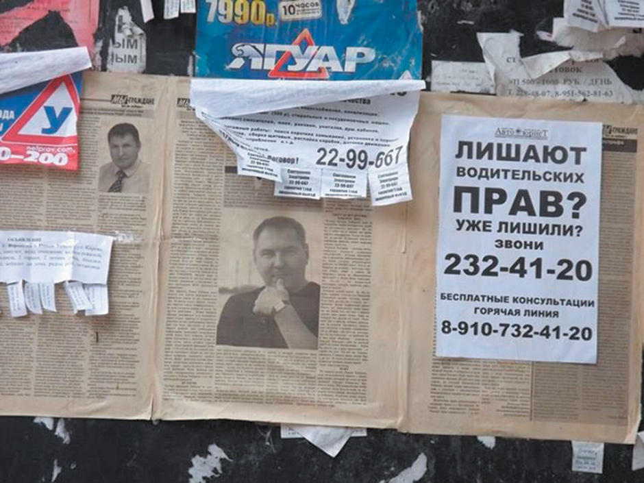 A weathered newspaper article on a wall in the Russian city of Voronezh, with a photograph of the local human rights activist Roman Khabarov, October 2013. The ad on the right reads, 'Are they taking away your driver's license? Or have they already? Call 232-41-20.'