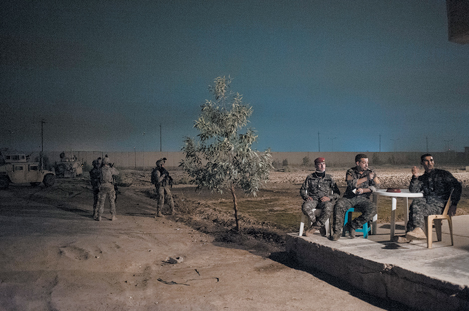 Iraqi policemen and American soldiers waiting while their commanders plan a joint patrol of southern Baghdad, 2010; photograph by Peter van Agtmael from his book Disco Night Sept. 11, published by Red Hook Editions