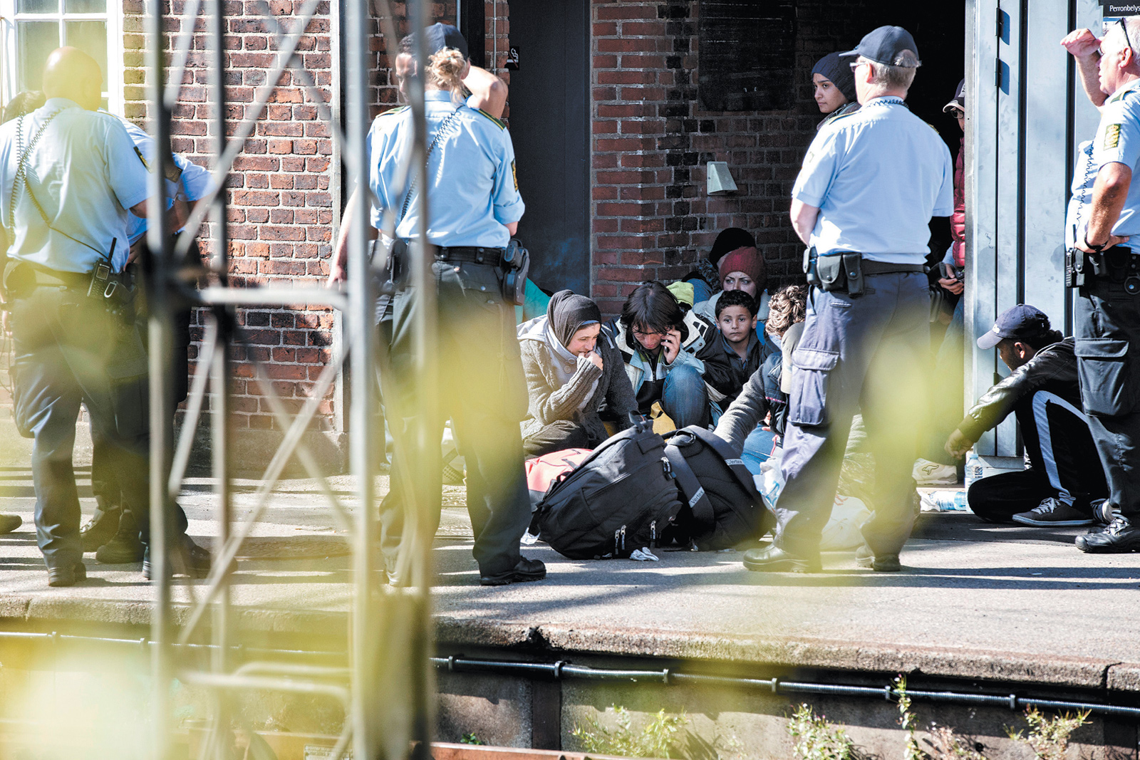 Police officers guarding refugees at Padborg Station, Denmark, after they entered the country from Germany, September 2015