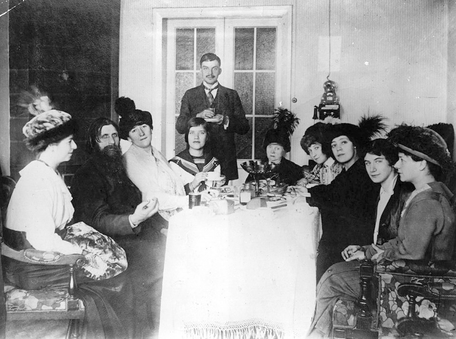 Rasputin with some of his admirers, St. Petersburg, circa March 1914. Among them xare Tsarina Alexandra's close friend Lily Dehn (third from left), Rasputin's daughter Maria (fourth from left), and Munya Golovina (far right), a devoted disciple who introduced Rasputin to Felix Yusupov, one of his killers.