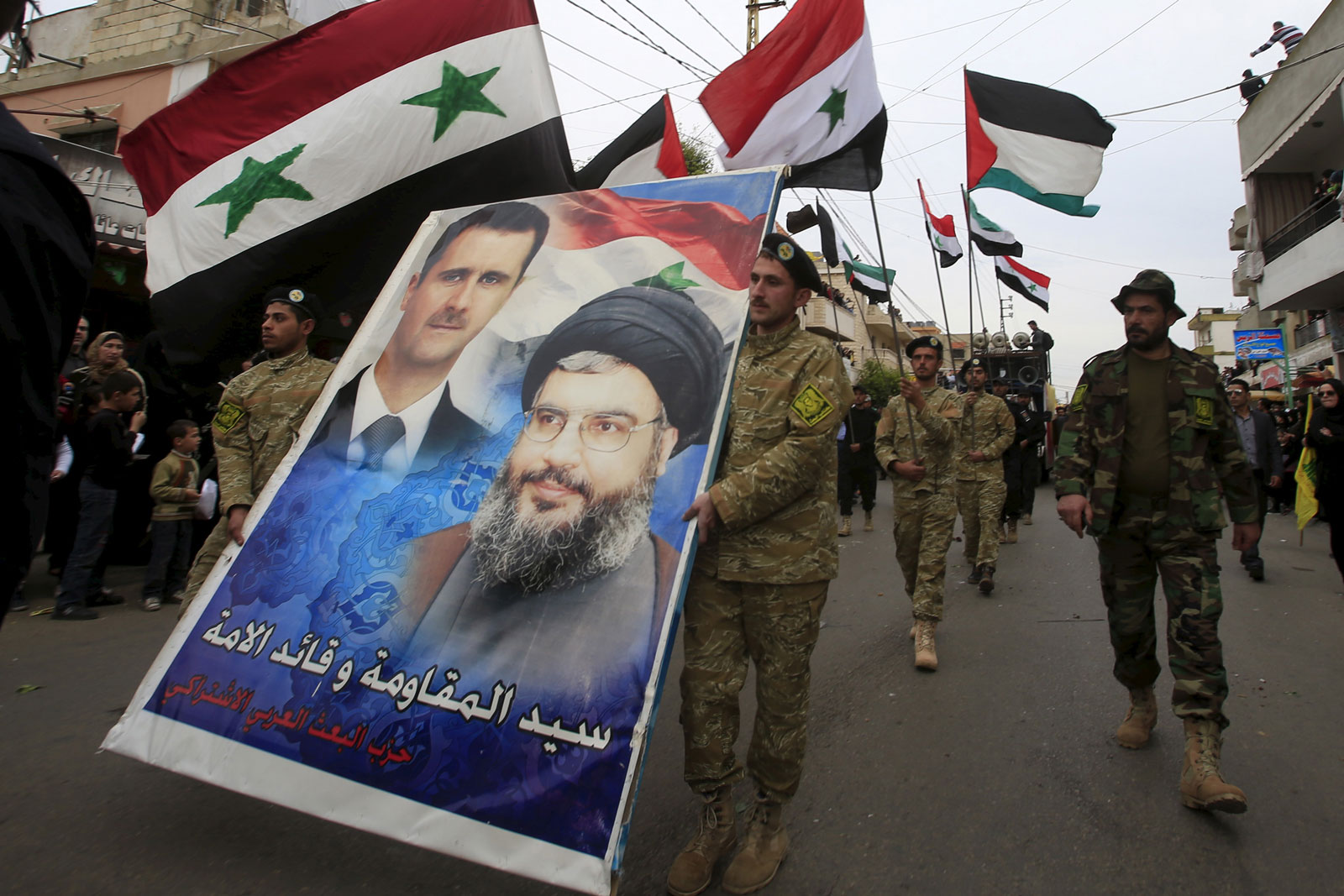 Supporters of the Syrian regime carrying a poster of Bashar al-Assad and Sayyed Hassan Nasrallah, the leader of Iran-backed Hezbollah, Ansar village, Lebanon, March 2, 2016