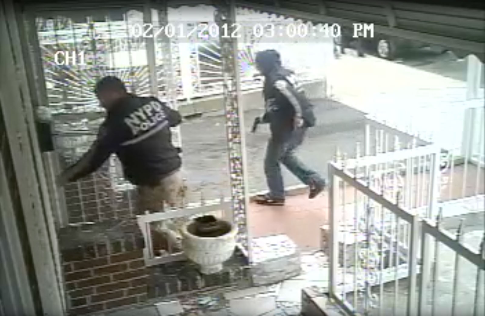 A still from the video surveillance footage taken outside Ramarley Graham's family home showing Officer Richard Haste trying to enter and another NYPD officer, gun drawn, February 2, 2012