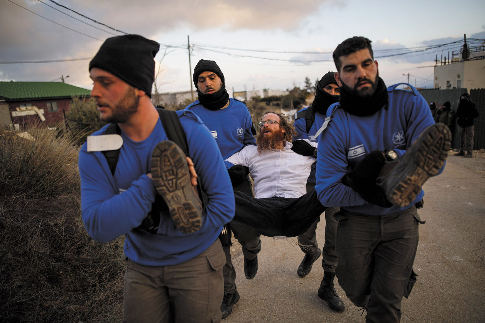 Israeli policemen removing a protester during the eviction of Jewish settlers from the illegal settlement of Amona in the occupied West Bank, February 2017