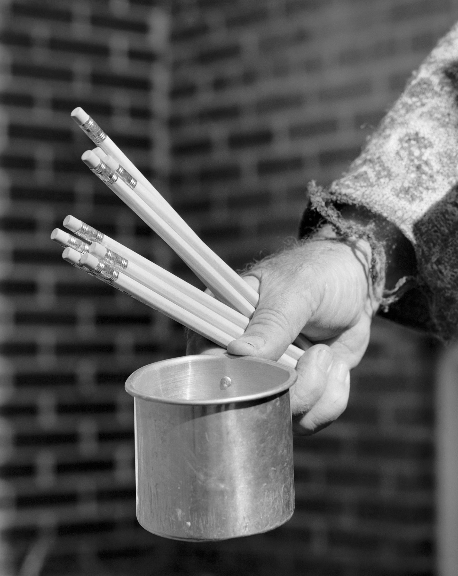 Close-up of a person's hand holding a mug and pencils