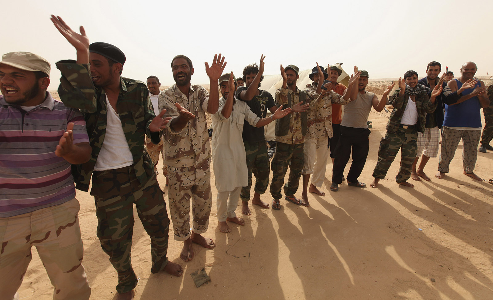 Rebel fighters celebrate on the front line, after hearing news that the ICC had issued an arrest warrant for Libyan leader Gaddafi