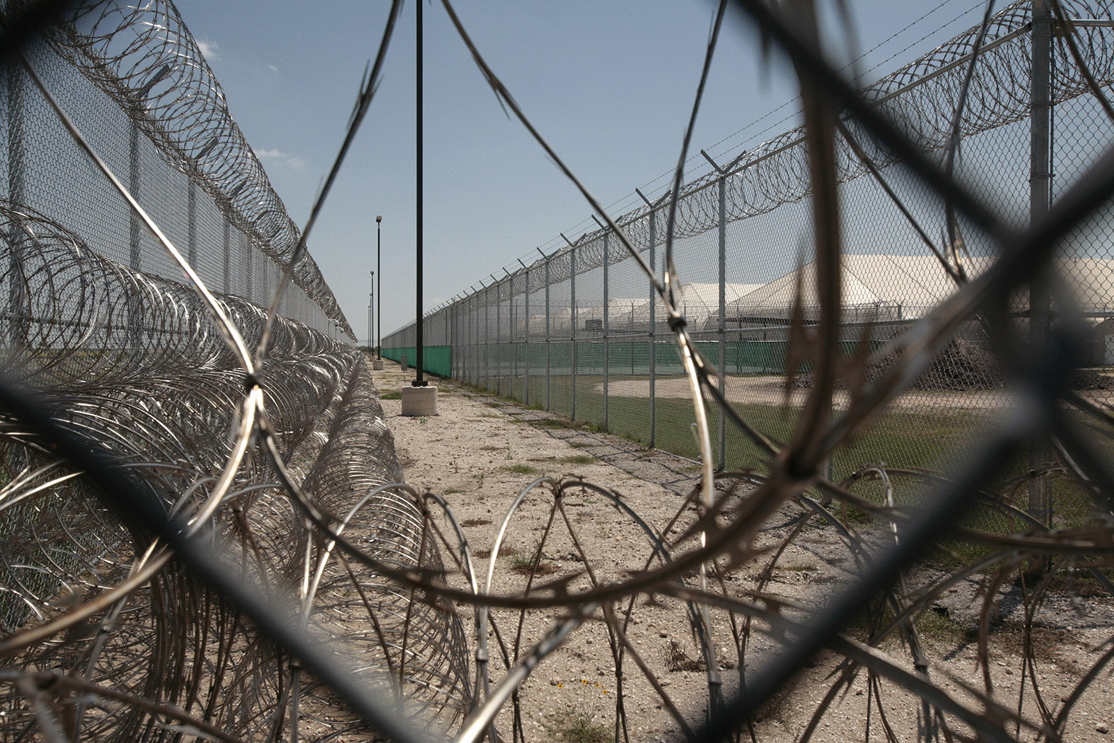Barbed wire, fences, and security cameras surrounding a tent city constructed in 2007 to house undocumented immigrants in Raymondville, Texas