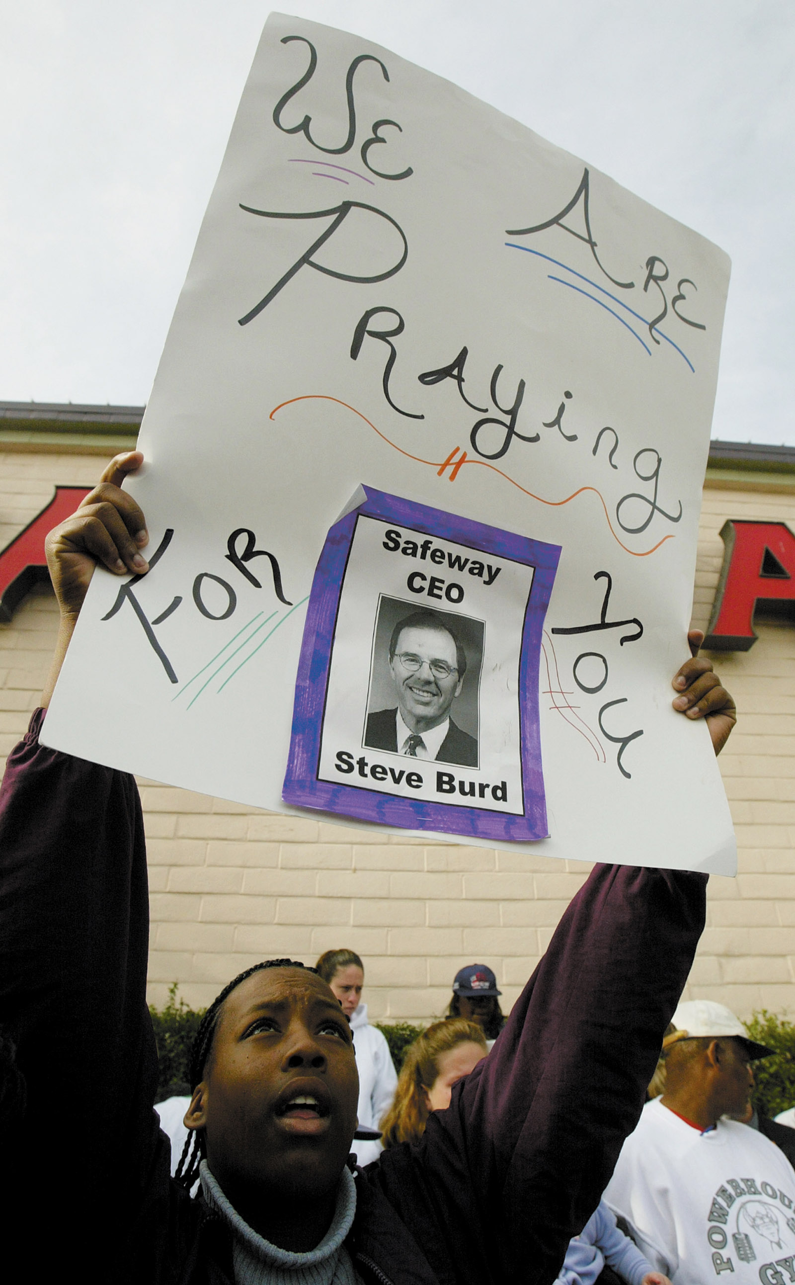 Supporter of striking grocery workers holds a sign, Alamo, California, January 2004