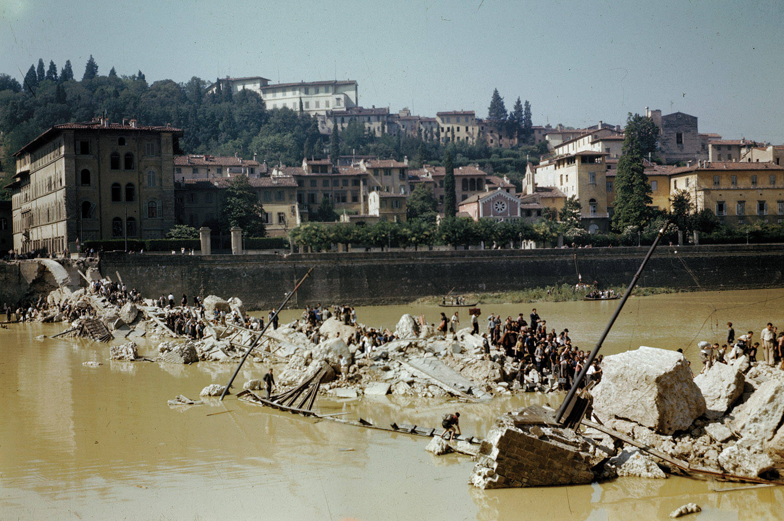 Italian civilians crossing the Arno River over the ruins of a bridge destroyed by German forces, Florence, August1944