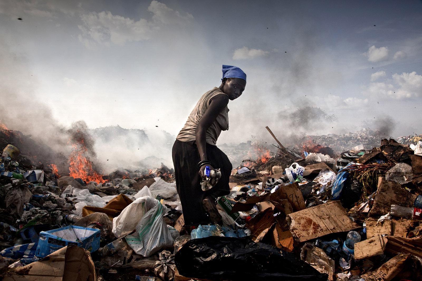 A woman walking through the landfill where she lives, Juba, South Sudan, 2010