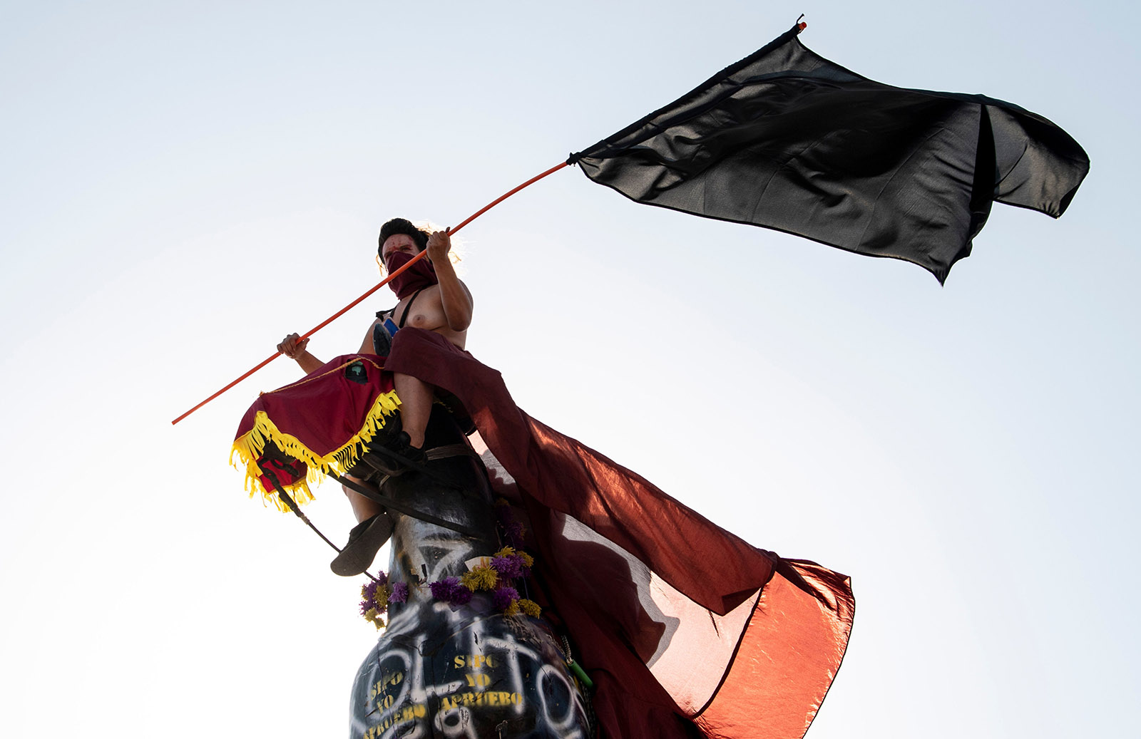 A protester astride the statue of General Baquedano at an International Women's Day demonstration, Santiago, Chile, March 8, 2020