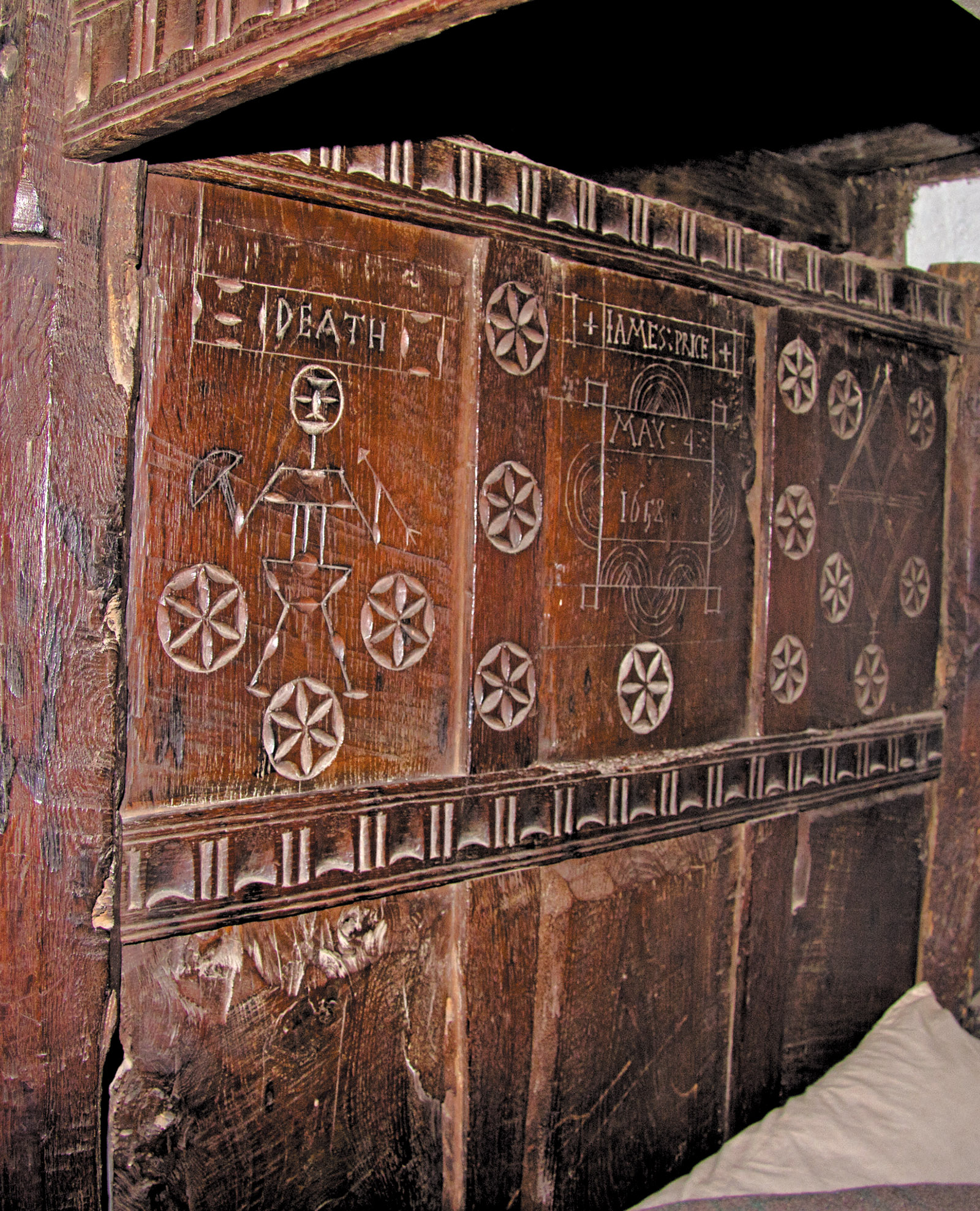 A headboard from a Welsh farmhouse engraved with symbols