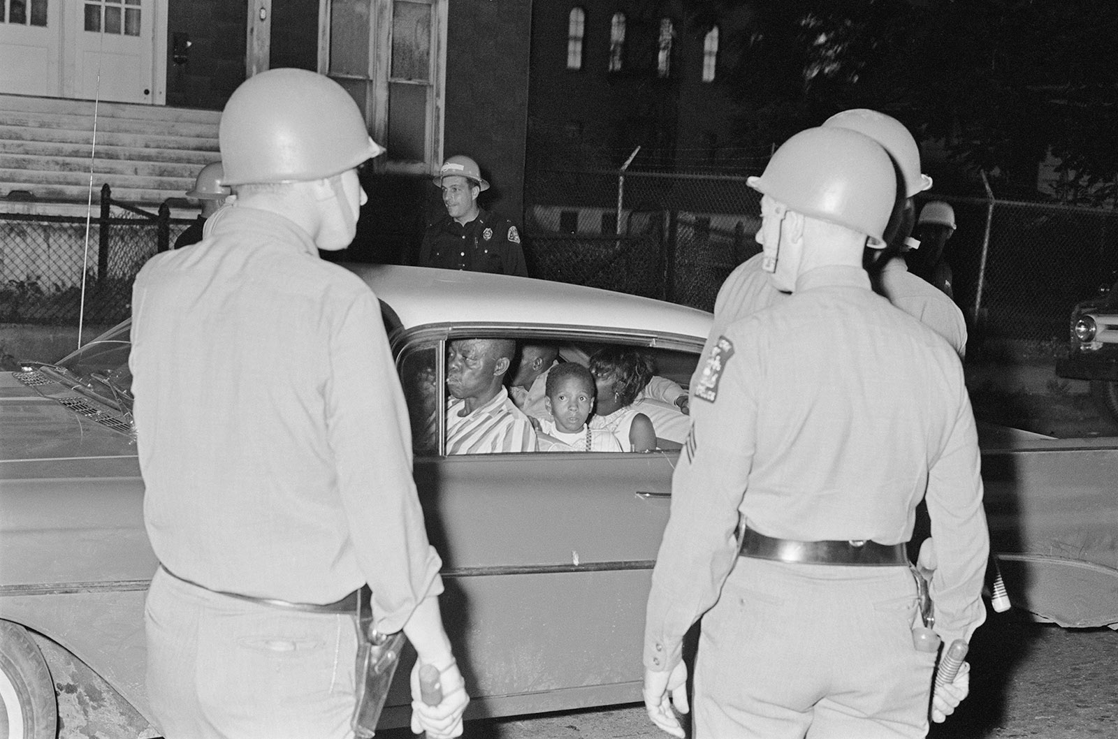 New York State Police officers stopping a black family during the Rochester race riot, July 1964