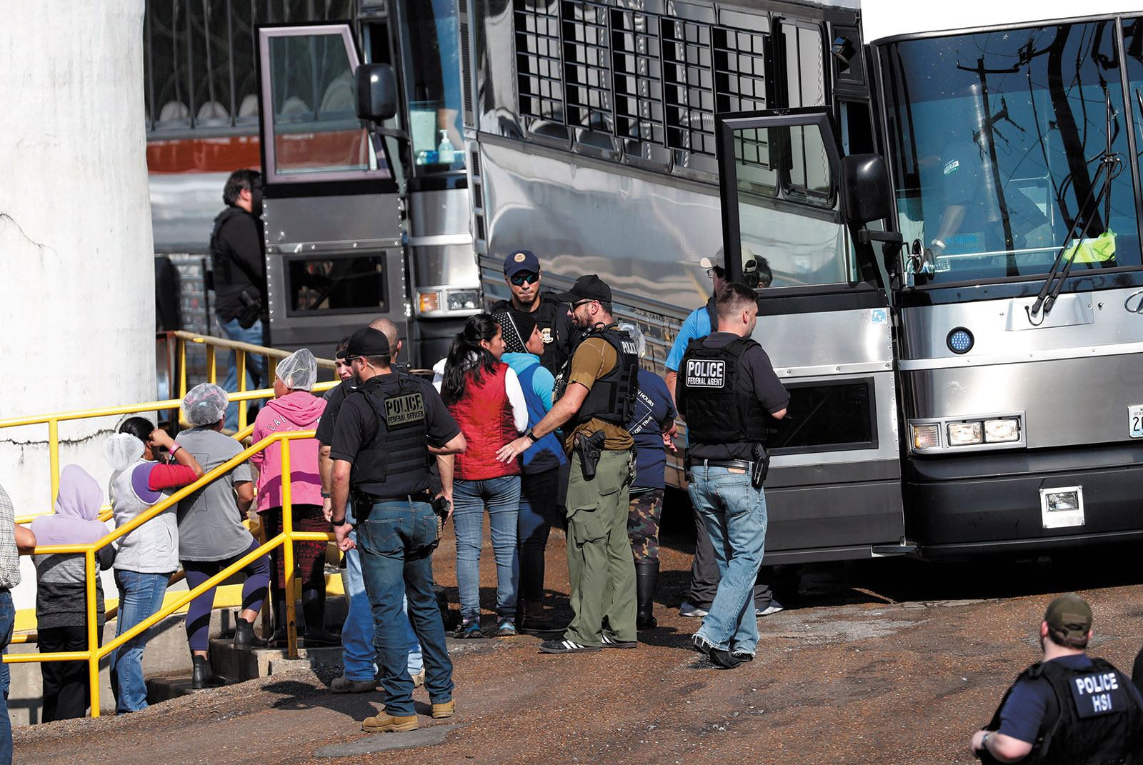 Workers from a Koch Foods plant being taken away by ICE agents during a raid, Morton, Mississippi, August 7, 2019