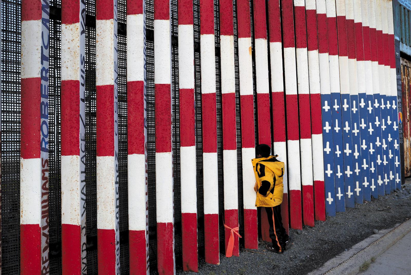 A migrant child looking through the US-Mexico border fence, Tijuana, November 2018