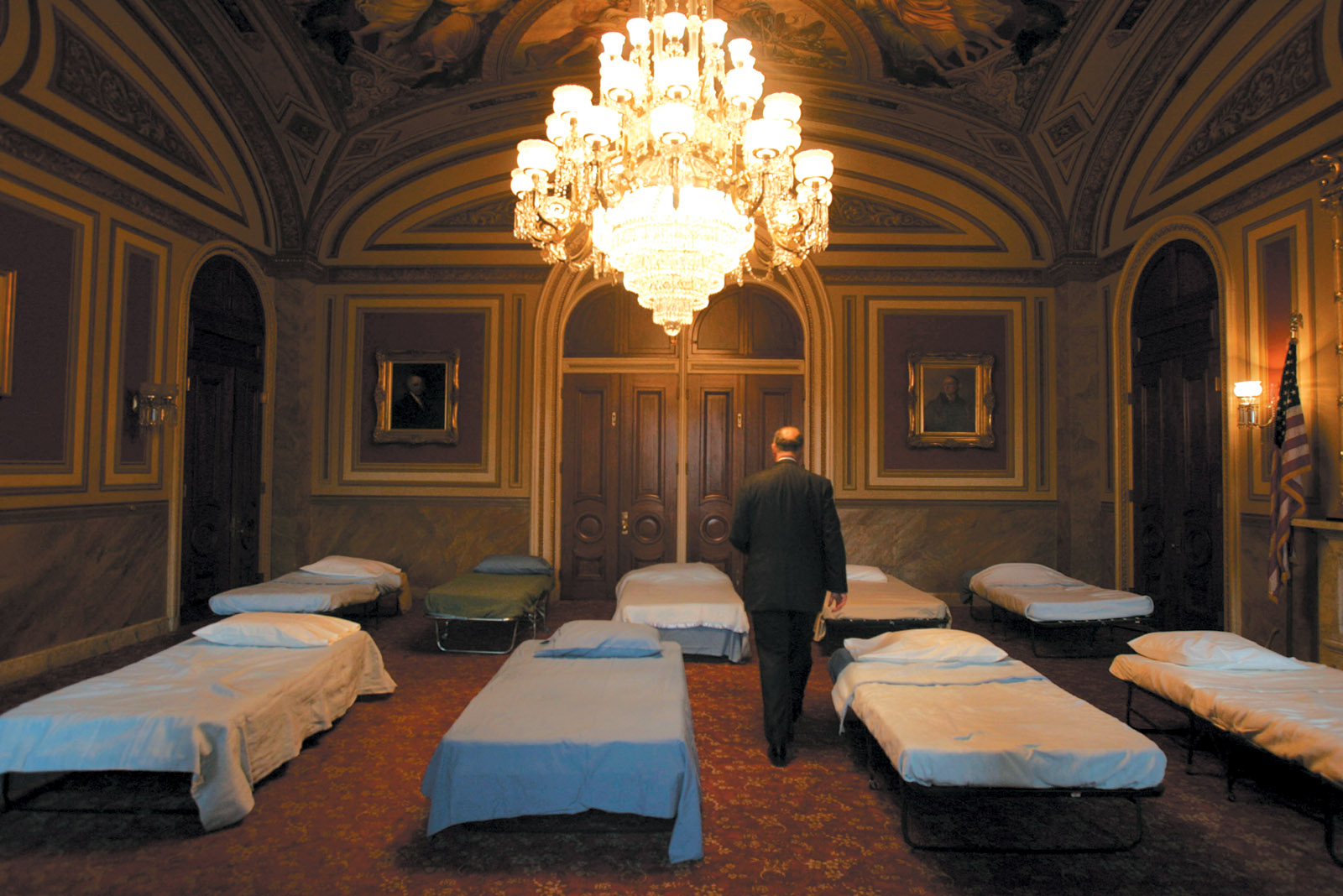 Senator Chuck Schumer walking to the Senate floor through a room filled with cots in preparation for an all-night debate