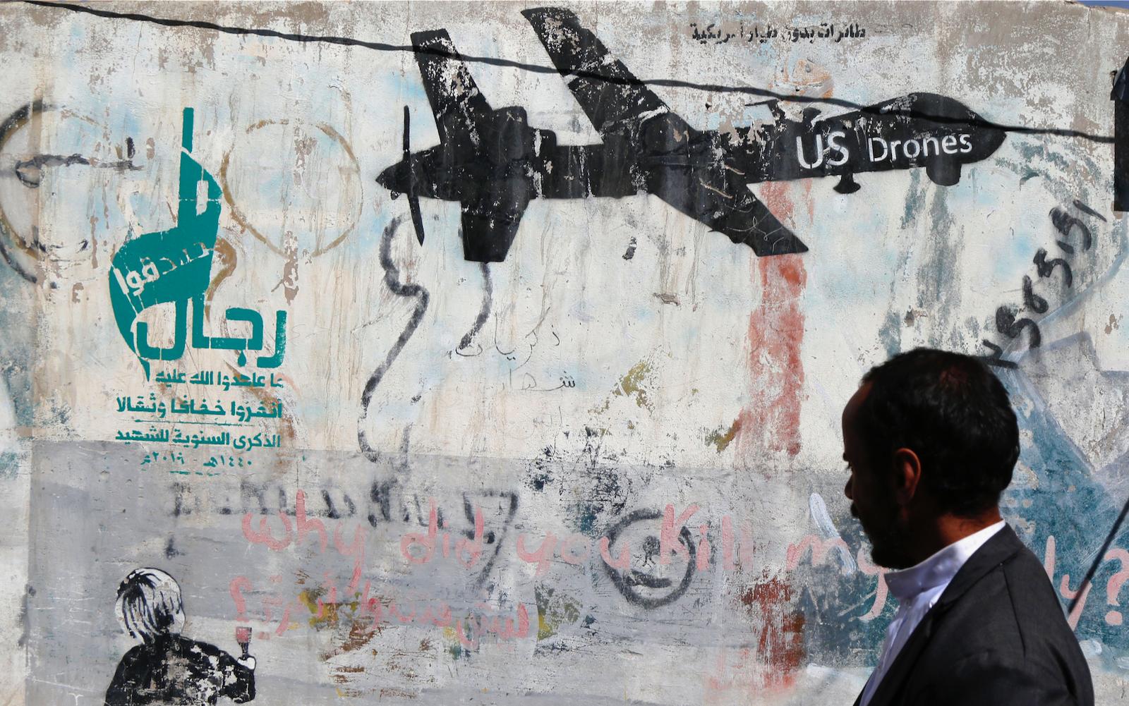 A man passing a wall with graffiti in Sana'a, Yemen
