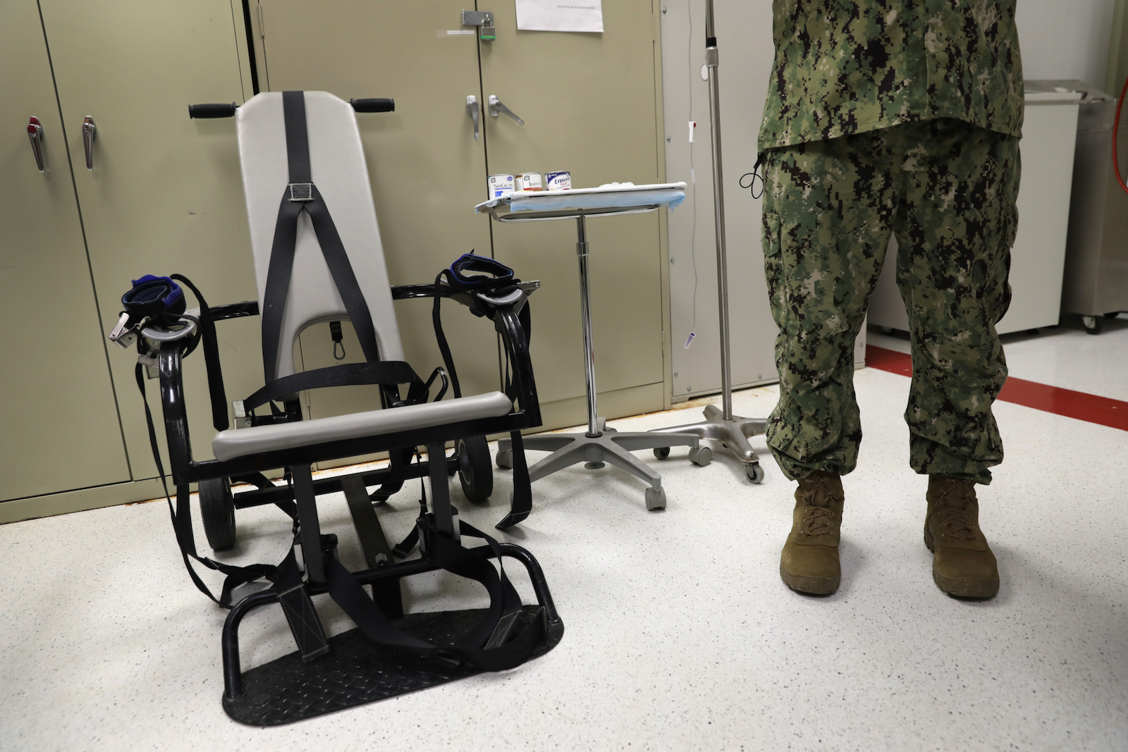 A US Navy doctor with a restraint chair used to force-feed detainees